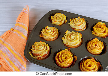 Baked potato roses with a bacon in oven pan