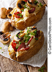 Baked potato stuffed with bacon, mushrooms and cheese close-up. vertical