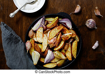 Baked potatoes in a pan with onions