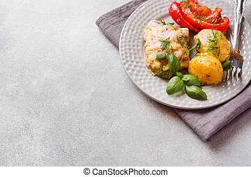 Baked potatoes with chicken and vegetables on a plate. Copy space.