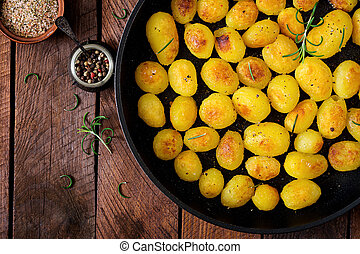 Baked potatoes with rosemary and pepper in a frying pan on...