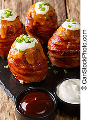 Baked potatoes wrapped in bacon topped with cheese and sour cream close-up. vertical