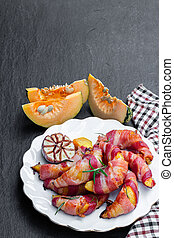 Baked pumpkin slices wrapped in bacon on black stone background