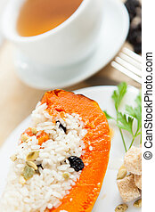 Baked pumpkin with rice and raisins and cup of tea