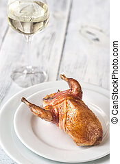 Baked quail wrapped in bacon on the plate