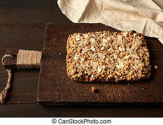baked rectangular crumble cake with fruit filling on wooden board