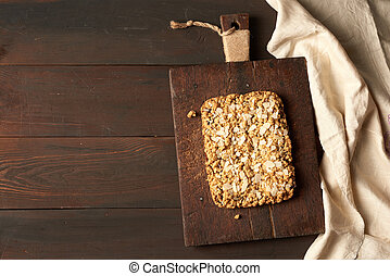 baked rectangular crumble cake with fruit filling on wooden board, brown background