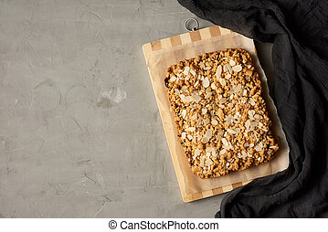 baked rectangular crumble cake with fruit filling on wooden board, gray background, top view