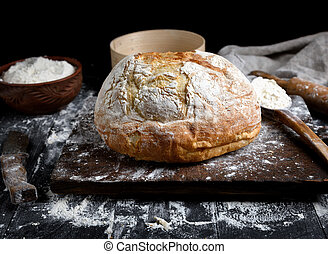 baked round white wheat bread on a brown wooden board
