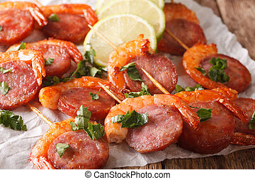 Baked shrimp and chorizo on skewers with fresh herbs close up. horizontal