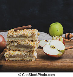baked slices of pie with apples on a brown wooden board