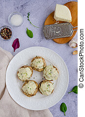 Baked Stuffed mushrooms with onion, cream, garlic, thyme and cheese on a white plate. Vertical orientation. Top view.