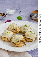 Baked Stuffed mushrooms with onion, cream, garlic, thyme and cheese on a white plate. Vertical orientation.