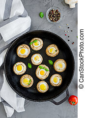Baked stuffed mushrooms with quail eggs with thyme leaves and basilin in an old cast-iron frying pan on a dark concrete background. Easter appetizer. Vertical orientation. Top view.