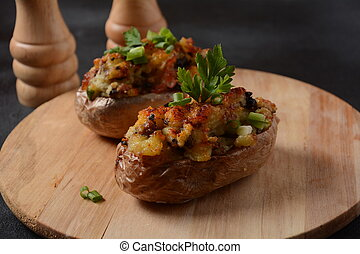 Baked stuffed potatoes with bacon, green onion,mushrooms and cheese on a wooden board. Rustic style