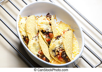 baked tacos filled with minced beef meat, beans and tomatoes