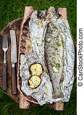 Baked trout with grilled potatoes on grill