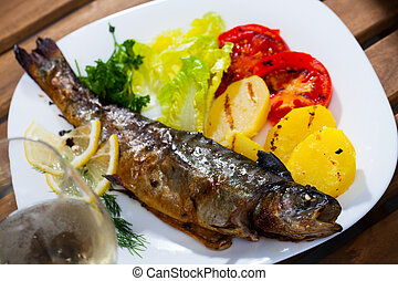 Baked trout with potatoes, tomatoes and white wine