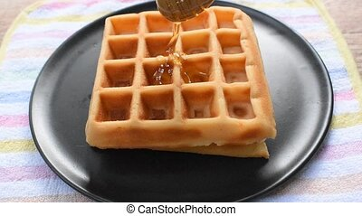 baked waffle dressing honey from wooden scoop on plate