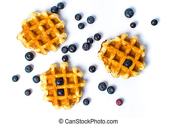 Baked waffles and blueberries isolated on white