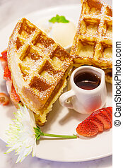 Baked waffles with syrup and strawberries