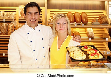 Baker and shopkeeper in bakery with tablet of cake - Baker ...