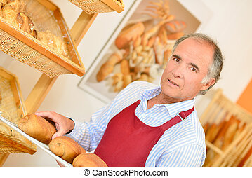 Baker carrying bread on a tray