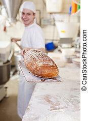 Baker carrying fresh baked bread