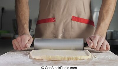 Baker chef roll the dough with the rolling pin on the table....