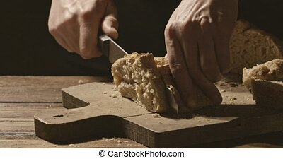 Baker cuts a piece of bread with a crispy crust on a cutting...