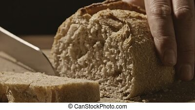 Baker cuts fresh white bread on a wooden board - Baker cuts...