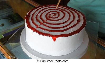 Baker decorating vanilla cake with strawberry sauce