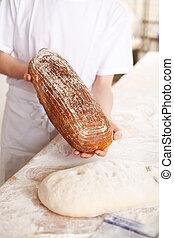 Baker displaying fresh bread
