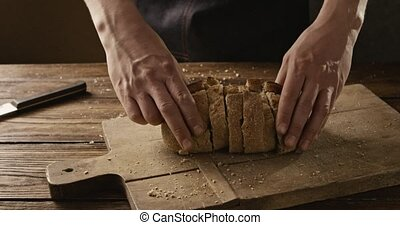 Baker folds pieces of fresh bread on a cutting board on an...