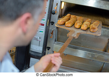 baker getting fresh bread out of the traditional oven