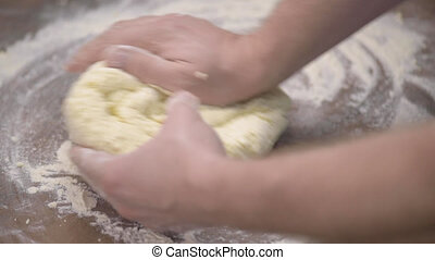 Baker Kneading Dough in Flour on the Kitchen Table. Man Chef Making Cookies at Home. Close up view of Man Hands Preparing Dough for Curd Pancakes.