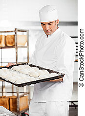 Baker Holding Baking Tray While Standing In Bakery
