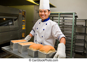 Baker holding fresh bread from oven - Male baker smiling...