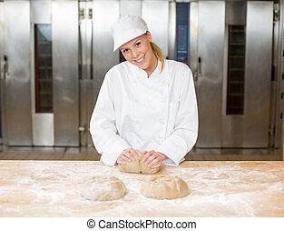 Baker in bakehouse or bakery kneading dough