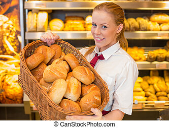 Baker in bakery with basket full of bread - Baker or ...