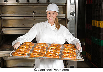 Baker in front of oven with pretzels inside a bakery -...