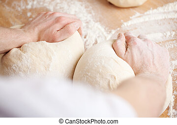 Baker kneading bread dough with one portion for a loaf under...