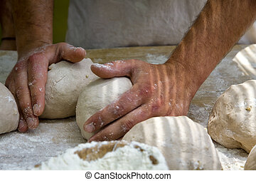 baker kneading bread - hands kneading bread dough on a...
