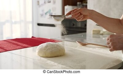 Baker kneading dough in flour on table. Close up of female...
