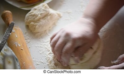 Baker kneading dough in flour on table