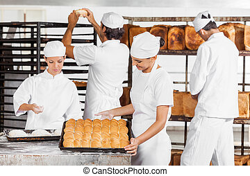 Baker Looking At Baked Breads In Bakery