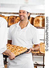 Baker Looking At Colleague While Carrying Bread Loaves