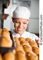 Baker Looking At Fresh Breads In Bakery