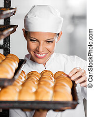 Baker Looking At Freshly Baked Breads In Bakery