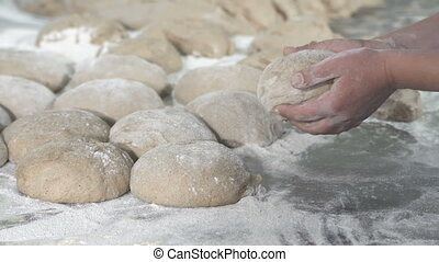 Baker packs dough for bread